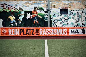 """Ein orangenes Banner mit der Aufschrift """"Kein Platz für Rassismus"""". Angebracht an der Spielfeldbarriere."""